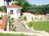 kleine Gartenlaube mit mediterranen Halbschalen eingedeckt