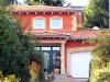 Mediterran gestalteter Eingangsbereich bei einer Stadtvilla. Der Putz ist im bordeaux gehalten. Saulen aus Sandstein sind auch zu sehen