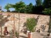 mediterrane Terrasse mit einer Mauer in heller grober Schieferoptik