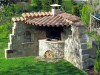Gartengrill in eine Natursteinmauer integriert mit Überdachung