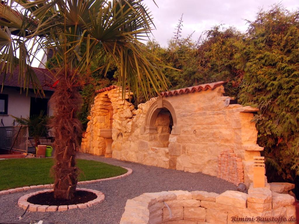 mediterraner Garten mit Bruchsteinmauer und Palmen