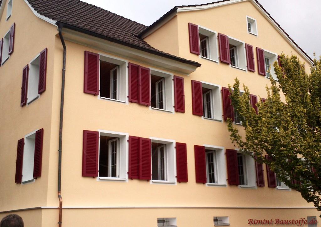 bordeauxfarbene Fensterlaeden zu einer gelben Putzfassade