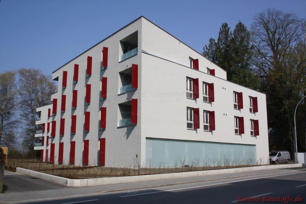Neubau eines Mehrfamilienhauses mit weinroten Fensterlaeden
