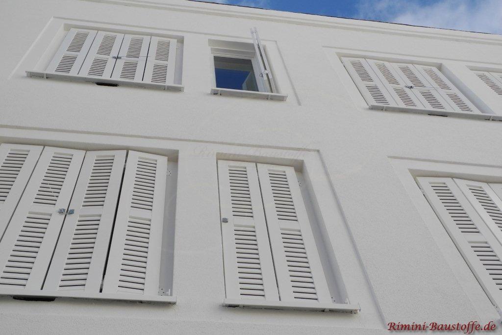 weisse Putzfassade und weisse Fensterlaeden