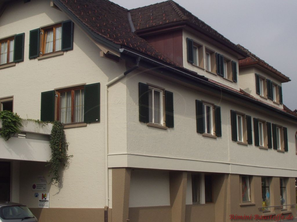helle Putzfassade und gruene Fensterlaeden