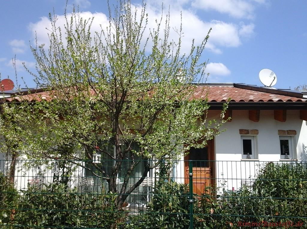 Bungalow mit weisser Putzfassade und mediterranen Dachziegeln