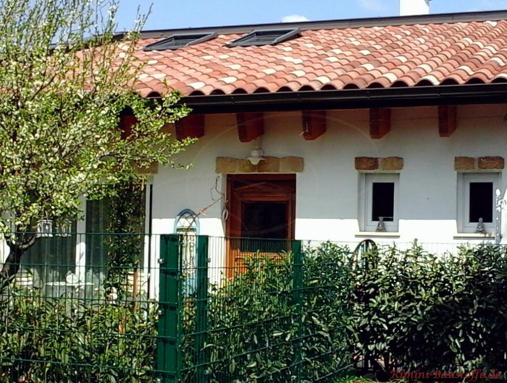 toller kleiner Bungalow mit weisser Putzfassade und mediterranem Dach