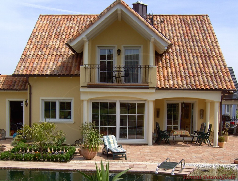 hellgelbe Putzfassade und ein milder romanischer Dachziegel