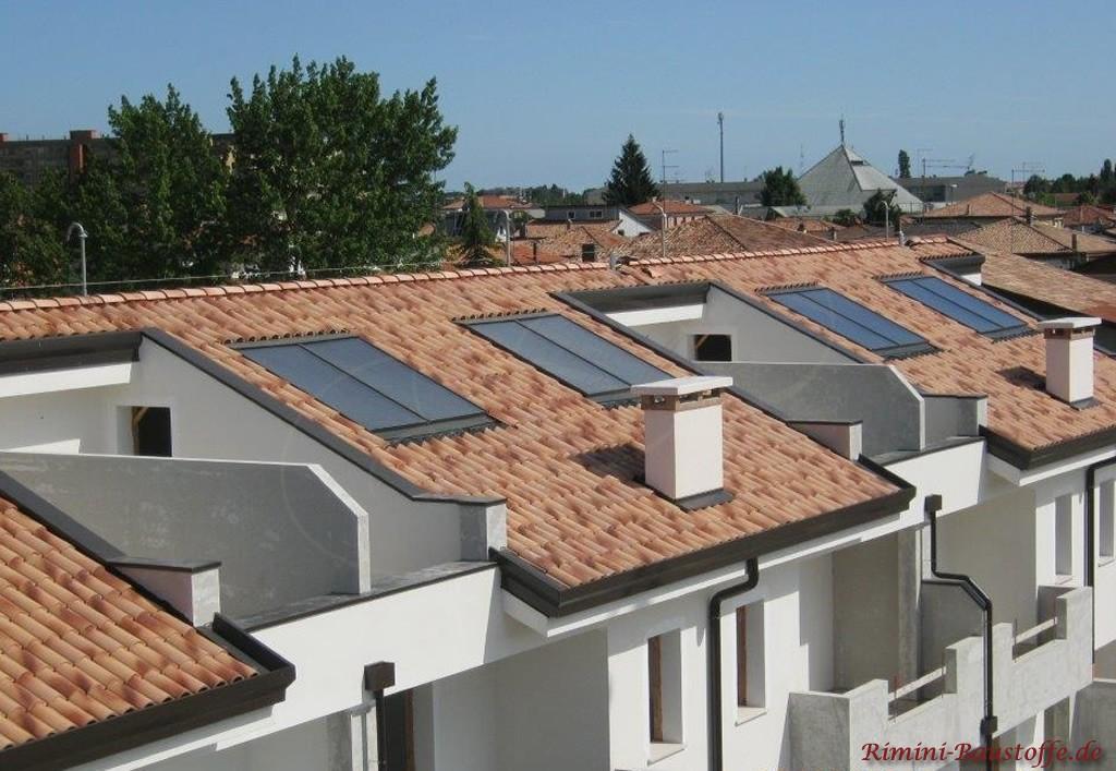 Wohnanlage mit weisser Putzfassade und mediterranem Dach