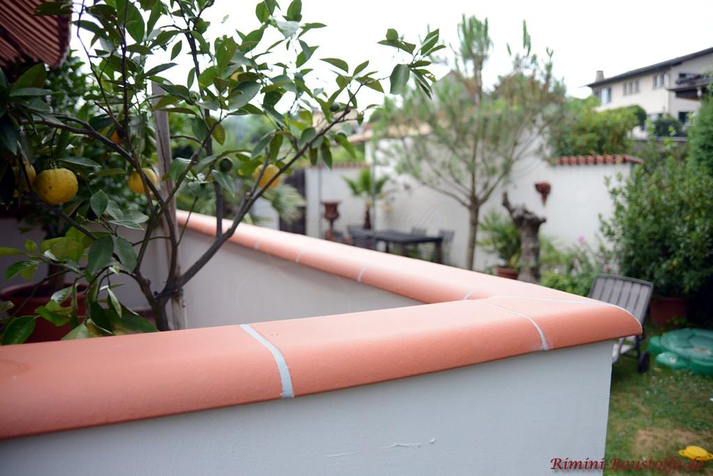weisse verputzte Balkonmauer mit einer Mauerabdeckung aus Ton