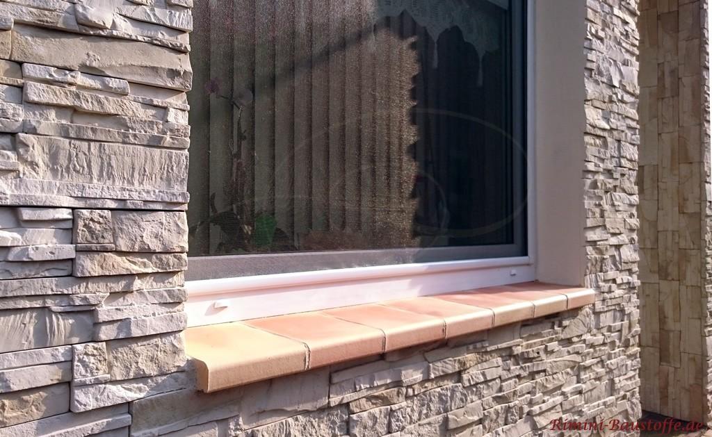 Fassade in Natursteinoptik und Fensterbaenke aus Ton