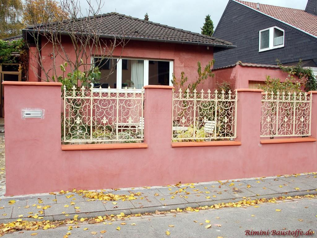 Rote Mauer mit integrierten Zäunen