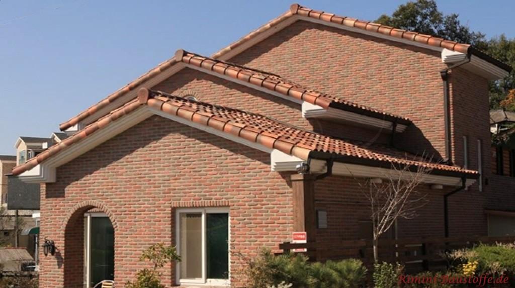 dunkler, mehrfarbiger Dachziegel zu einer Klinkerfassade