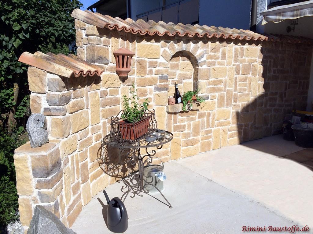 liebevoll gestaltete Gartenmauer im mediterranen Stil