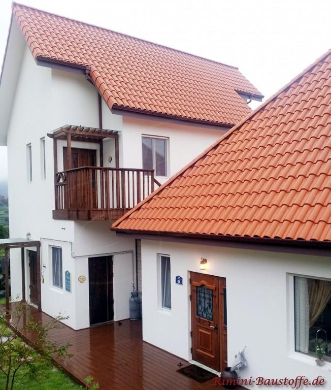 kraeftiger roter Tondachziegel zu einer weissen Putzfassade