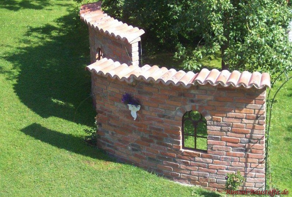 rustikale Klinkermauer mit Halbschalen und eiserne Fenster
