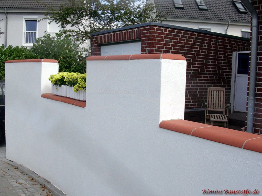 weiße Putzmauer mit schöner roter Mauerabdeckung