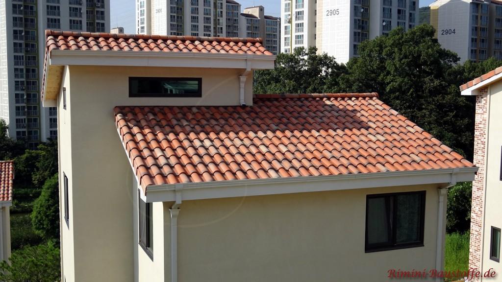 schoener roter Dachziegel zu einer hellen Putzfassade