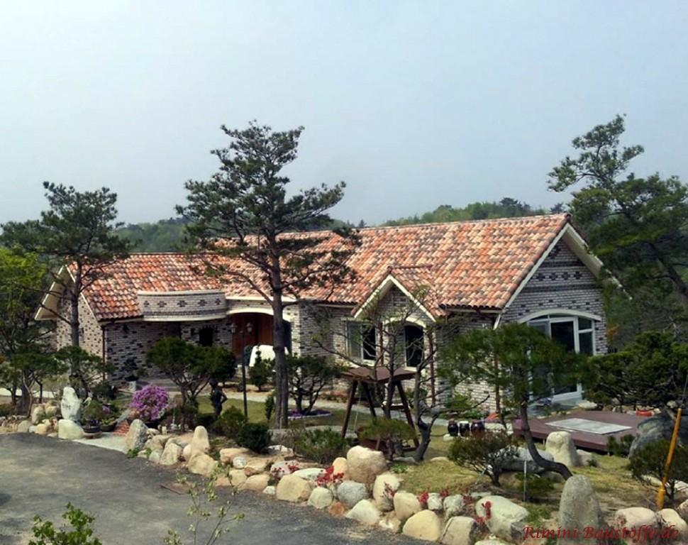 graue Klinkerfassade und ein bunter roter Dachziegel