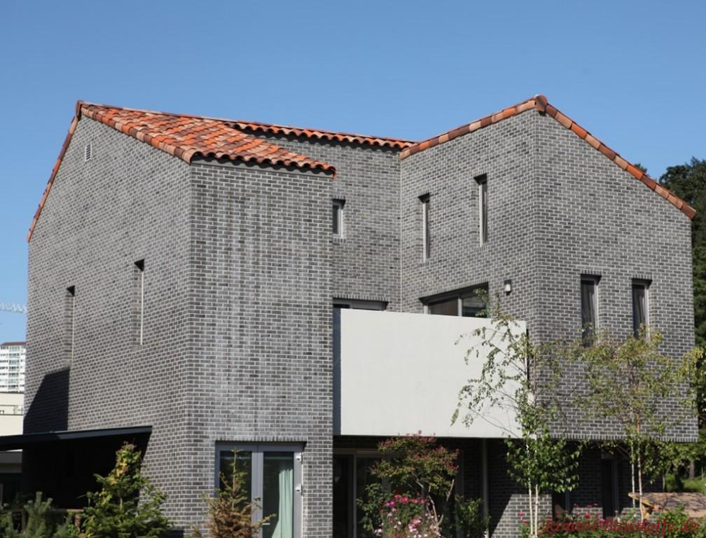 anthrazitfarbene Klinkerfassade und rotbunter Dachziegel