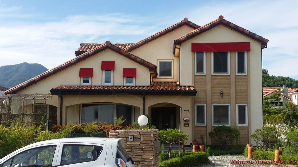 mehrfarbiger Dachziegel und eine helle Putzfassade