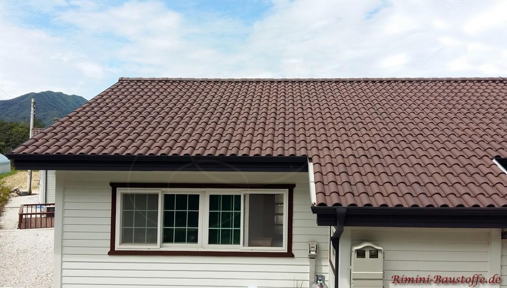 weisse Holzfassade und ein schoenes braunes Dach