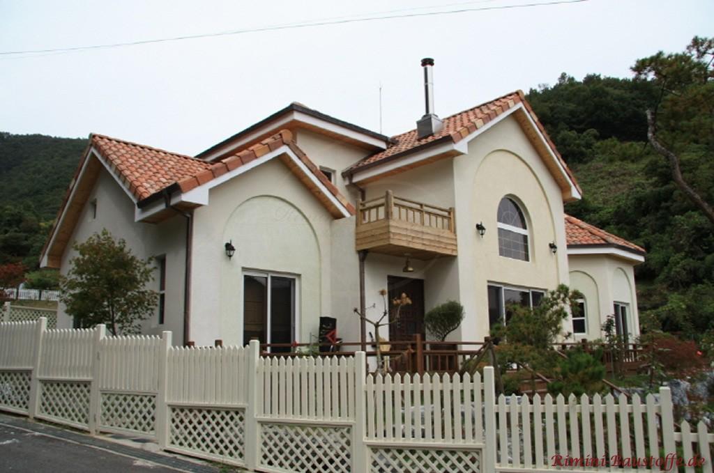 mediterrane Villa mit heller Putzfassade und rotem Dach