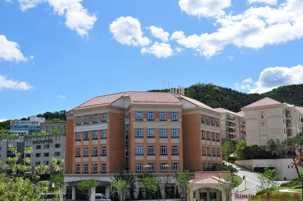 Hotelanlage mit roter Klinkerfassade und mediterranem Dachziegel