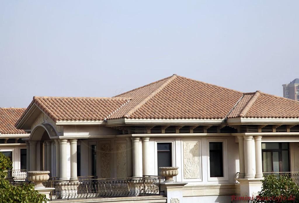 brauner romansicher Tondachziegel zu einer elfenbeinfarbenen Putzfassade