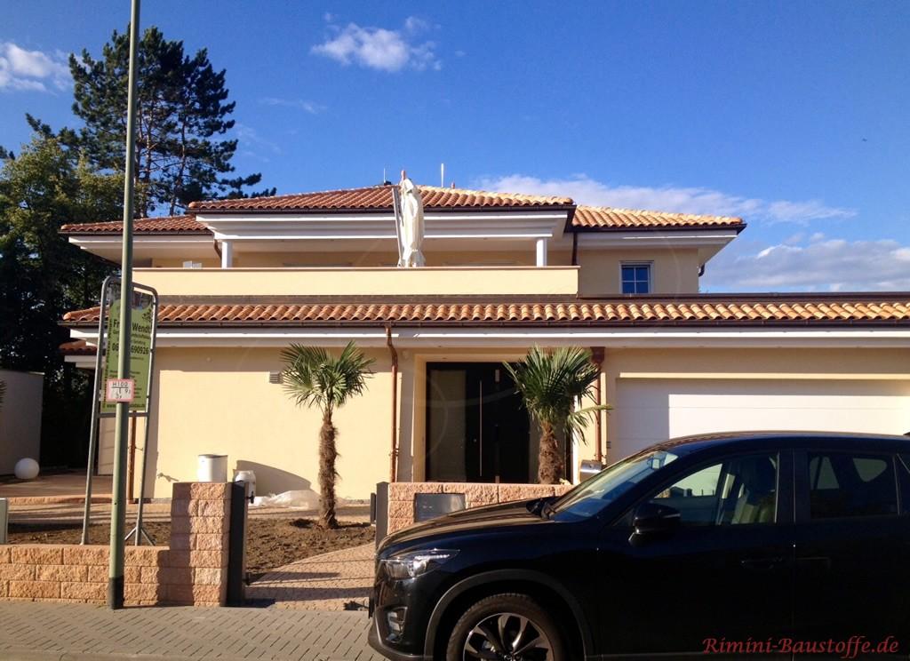 suedlaendische Villa mit gelber Putzfassade und mediterranem Dach