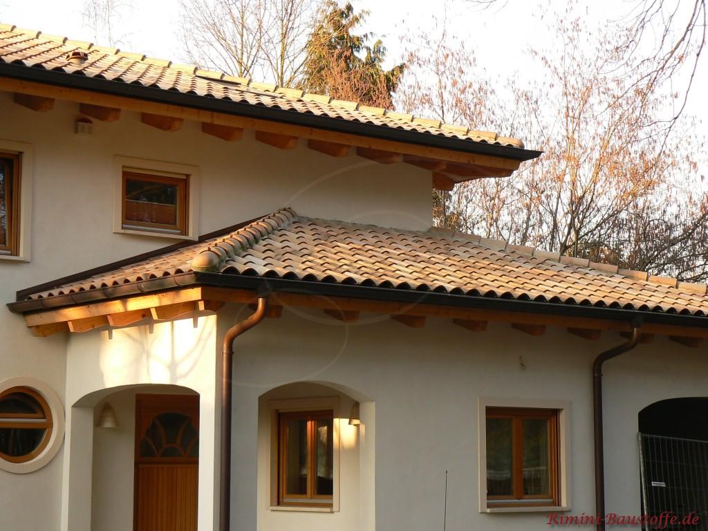 schoener mediterraner Dachziegel zu Holzfenstern und einer hellen Fassade