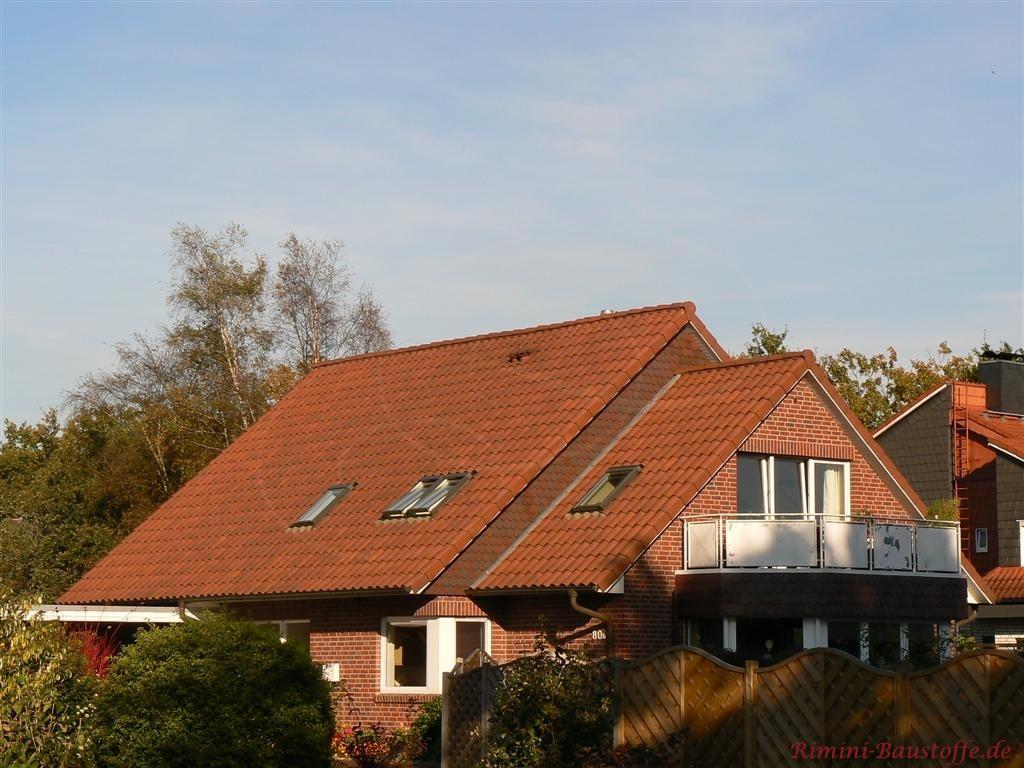 verklinkertes Haus mit rot changierenden Dachziegeln
