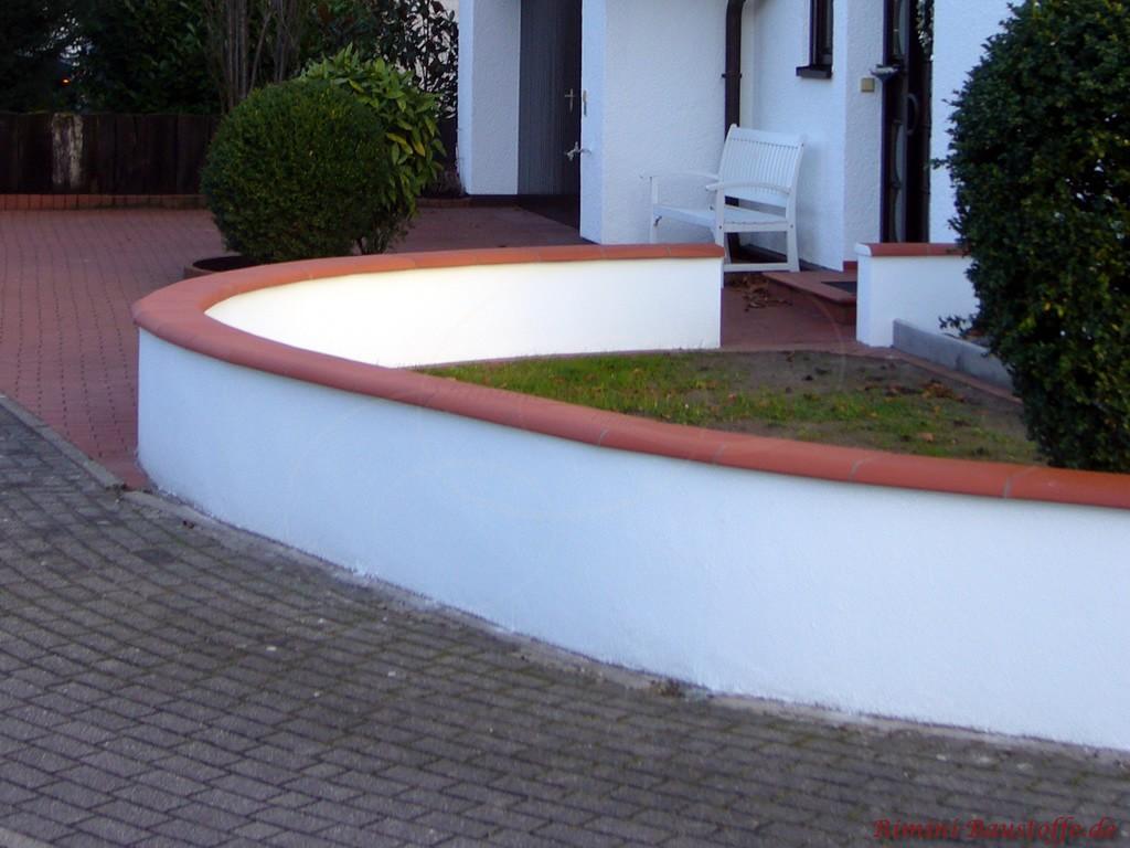 kleine weiße Putzmauer mit moderner roter Mauerabdeckung