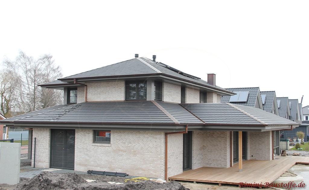 Neubau mit heller Klinkerfassade und einer Dacheindeckung aus Schindeln