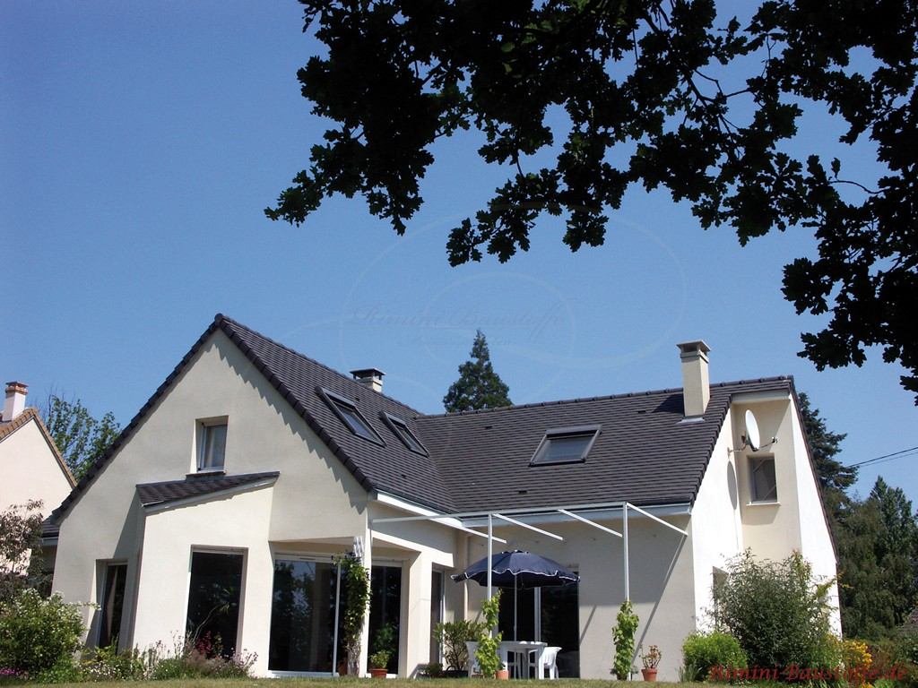 Einfamilienhaus mit weisser Putzfassade und schwarzer Schindel