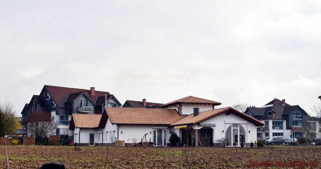 grosses Haus mit mehreren Satteldaechern und einem Turm
