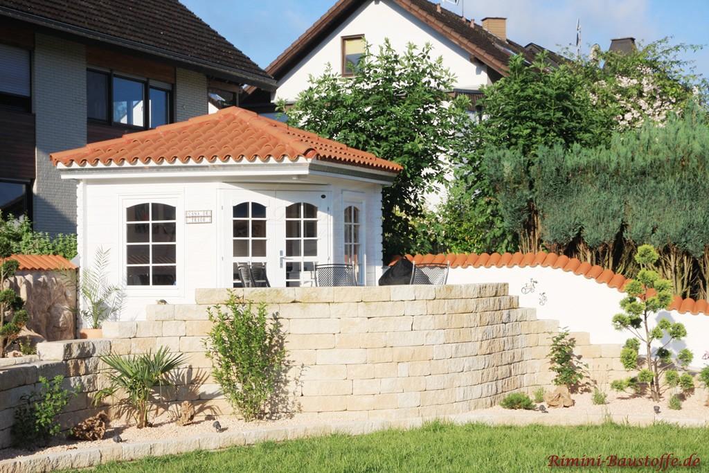 weisses Gartenhaus mit strahlend roten Halbschalen auf dem Dach
