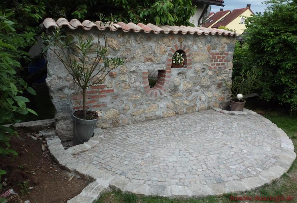 rustikale graue Mauer mit Halbschalen gedeckt