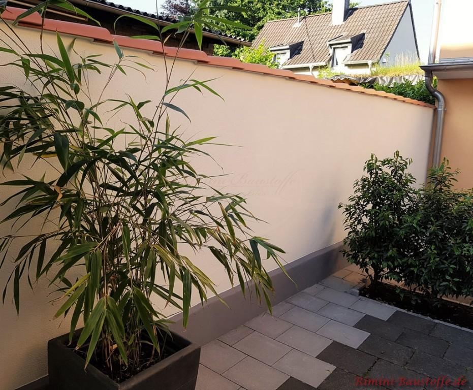 schmale Gartenmauer mit Halbschalen abgedeckt