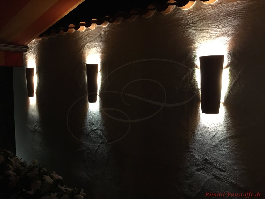 Tonhalbschalen als Wandlampen an einer Mauer