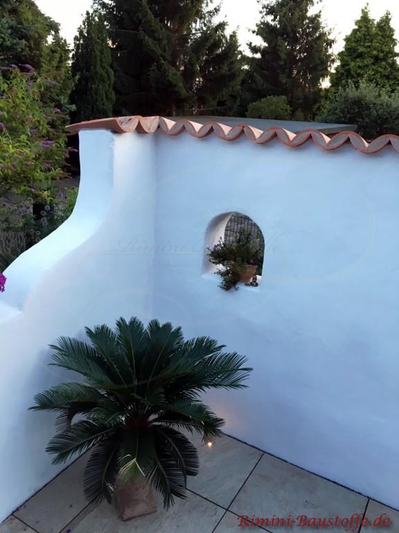 weiss verputzte Gartenmauer mit roten Halbschalen abgedeckt
