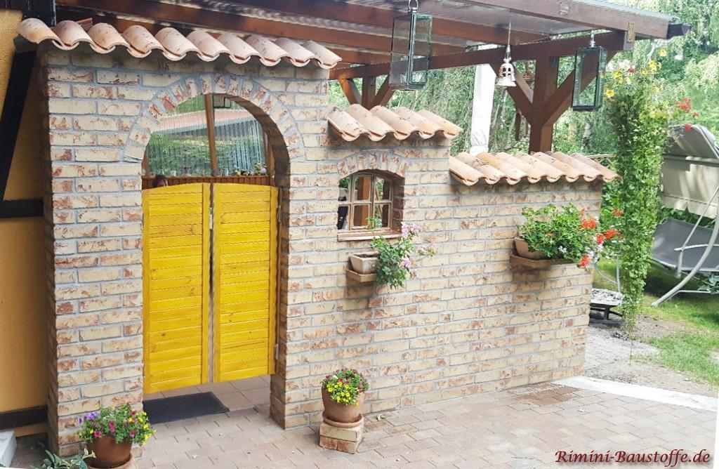 Gartenmauer mit gelber Schwingtuer wie in einem Saloon