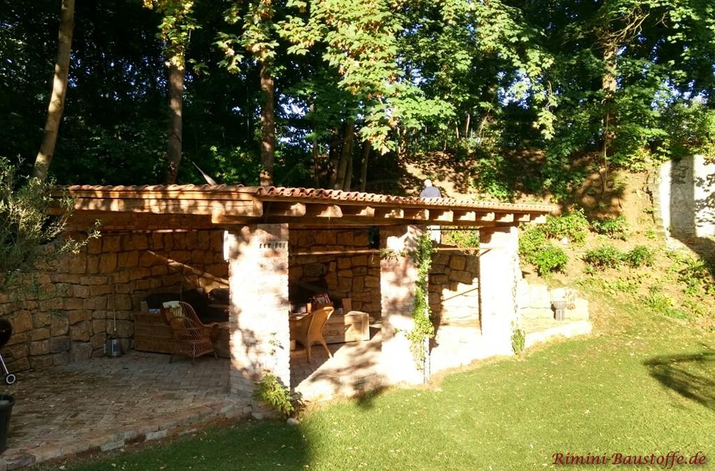 Gartenunterstand an einem Hang mit Natursteinen