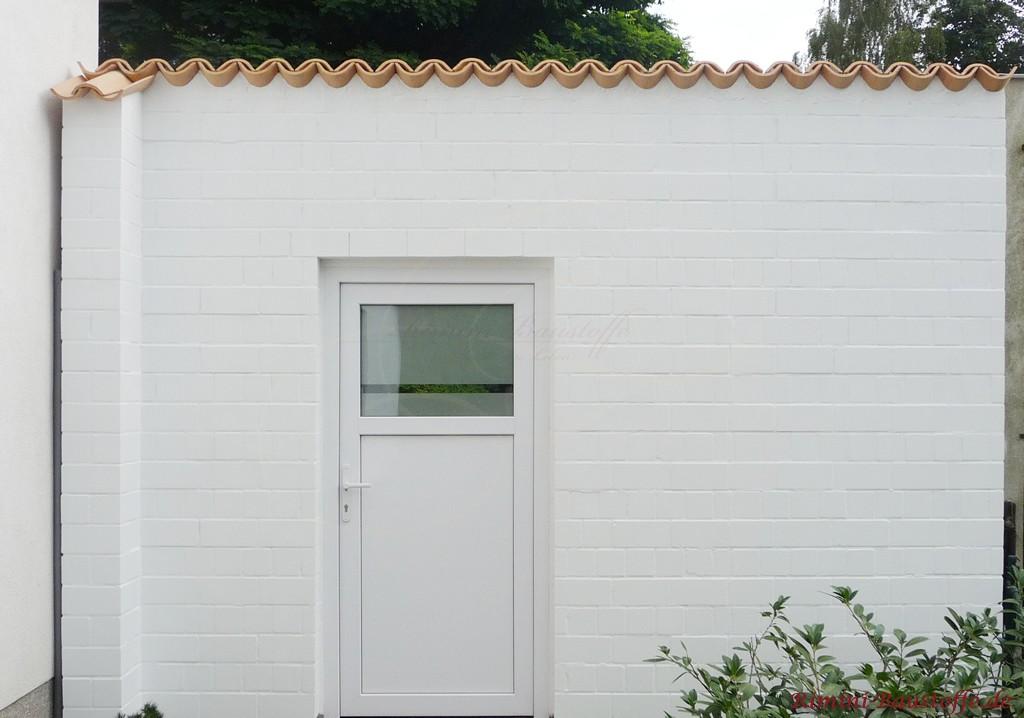 weiss gestrichene Gartenmauer mit beigen Halbschalen