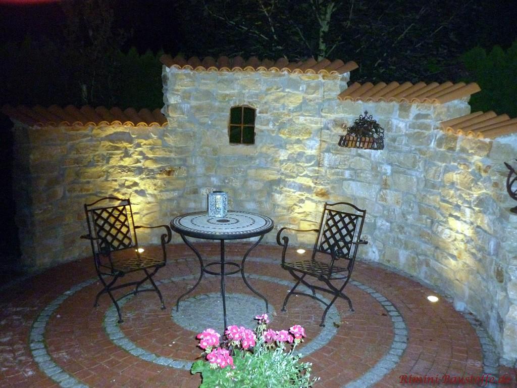 halbrunde Natursteinmauer mit Beleuchtung