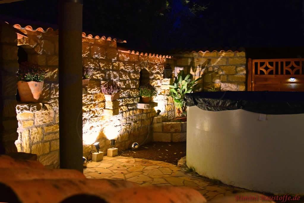 Natursteinmauer im Dunkeln mit Beleuchtung