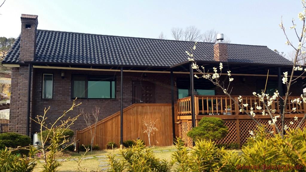 schwarzer Tondachziegel zu einer braun violetten Klinkerfassade