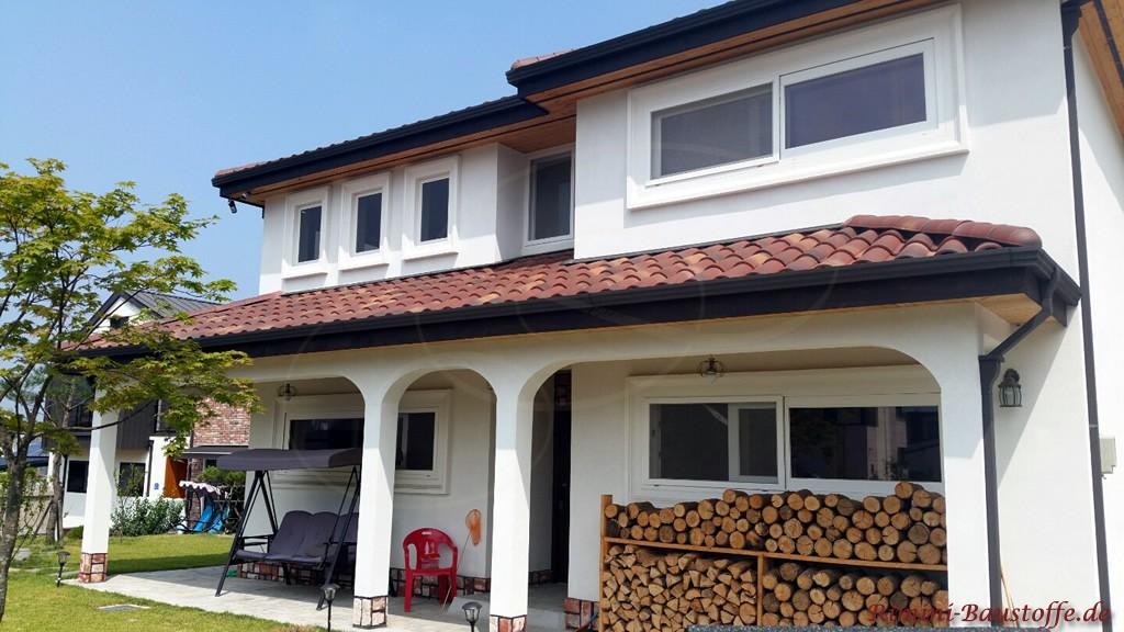 weisse Putzfassade und rotbraune Dachpfannen