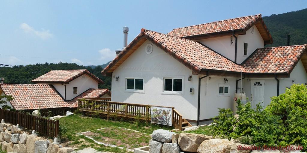Bungalow mit weisser Fassade und romanischen Dachpfannen aus Ton