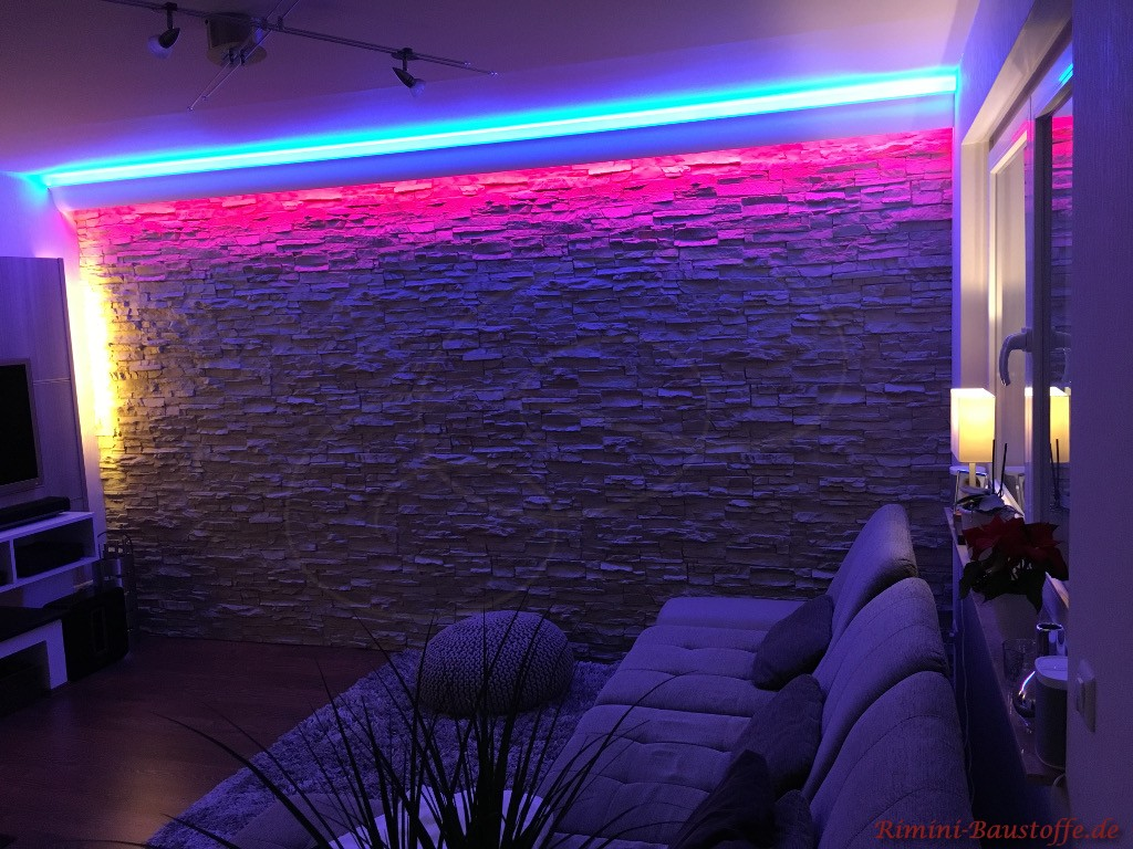 Wohnzimmerwand in Natursteinoptik mit farbiger Beleuchtung
